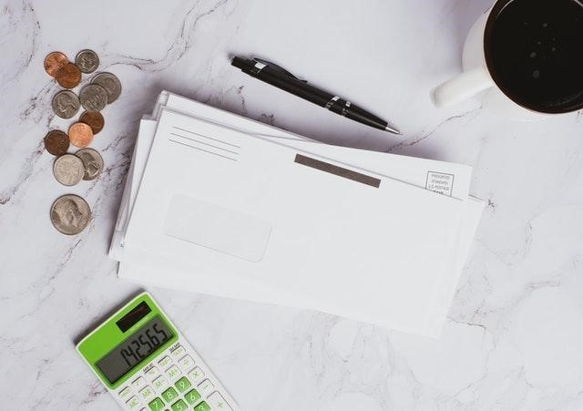 Envelopes, money, and a calculator on a marble countertop
